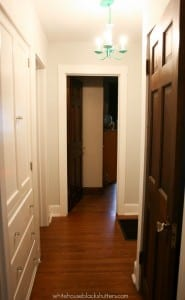 hallway with white trim and wood doors. WOW! What a transformation.