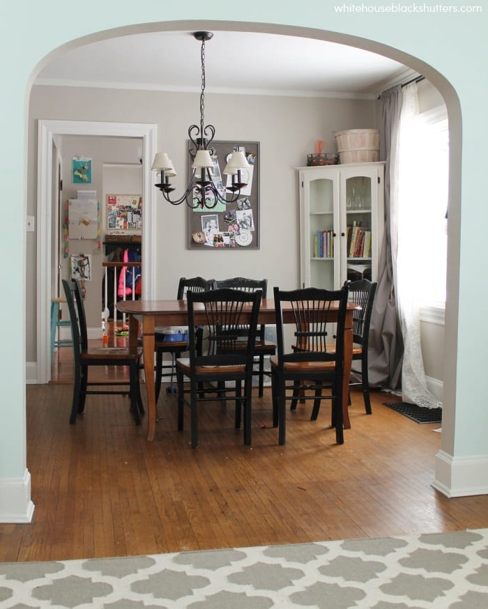 dining room with greige paint, white trim, black and white furniture.
