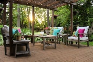 colorful outdoor space makeover using thrifted furniture, globe lights, and vivid pillows