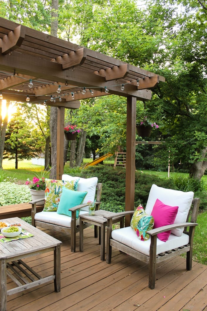 Epic colorful outdoor space makeover using thrifted furniture globe lights and vivid pillows