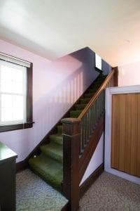 stairs going upstairs, dark wood green carpet