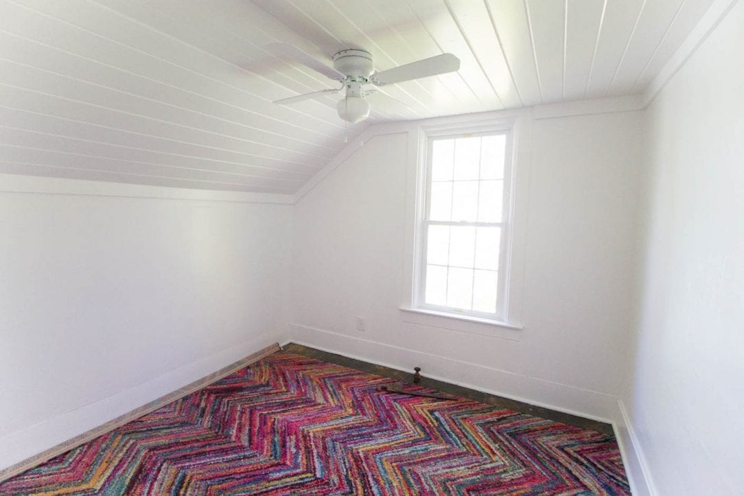 bright office remodel with white walls, planked ceiling, colorful rug